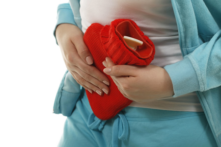 Schwangere mit roter Wärmflasche