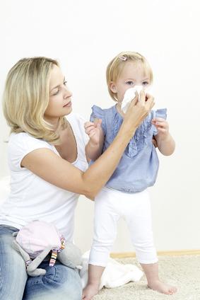 Mutter lässt Kind in ein Taschentuch schnäutzen