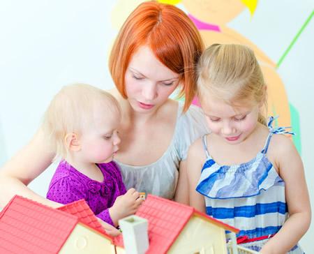 Tagesmutter mit zwei kleinen Maedchen