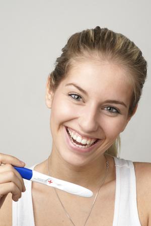 Frau mit positiven Schwangerschaftstest