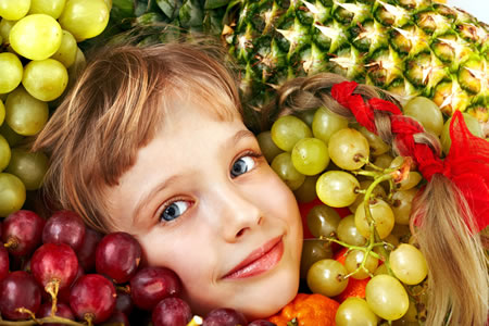 Kind mit Trauben,Kirschen und Ananas