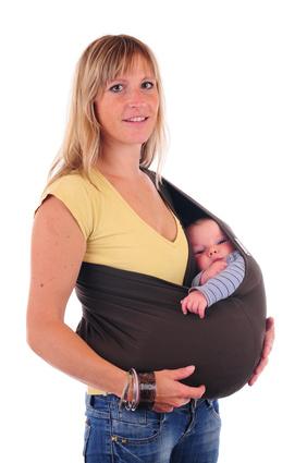 Mutter traegt Baby im Tragetuch