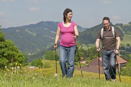 Schwangere wandert durch bergige Landschaft
