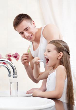 Vater und Tochter beim Zaehneputzen