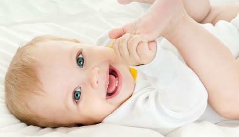 Ein lächelndes Baby zeigt erste Zähne