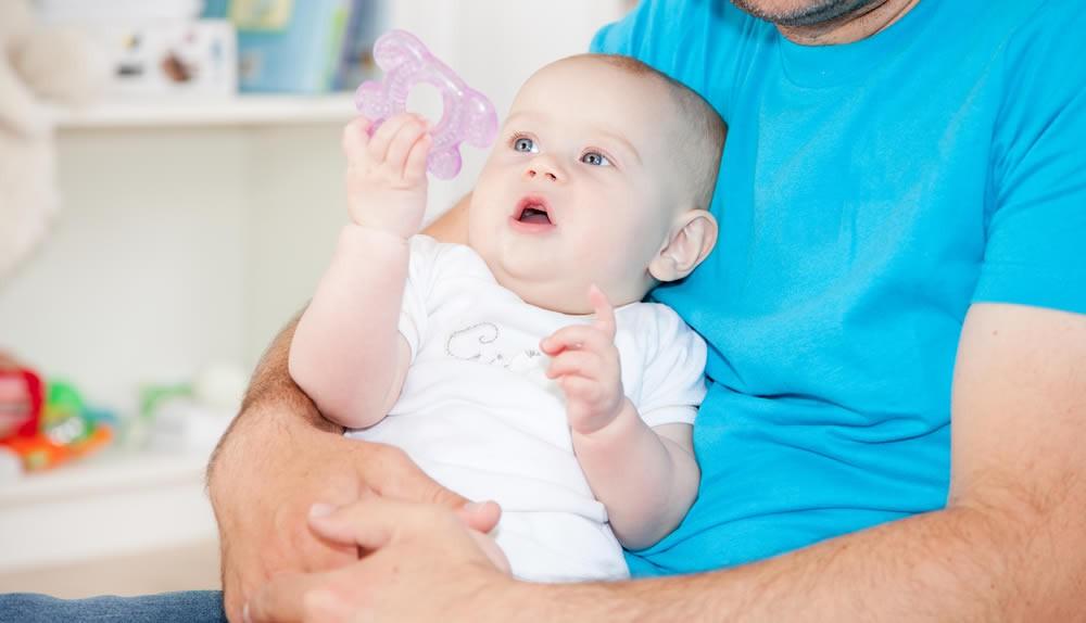 Ein Baby deutet fasziniert auf sein Spielzeug