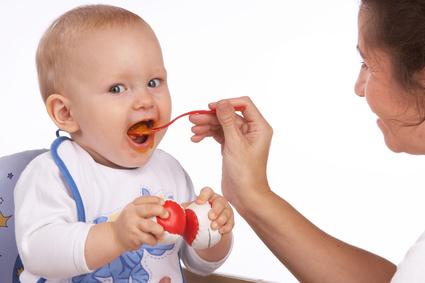Baby wird mit erstem Brei gefüttert