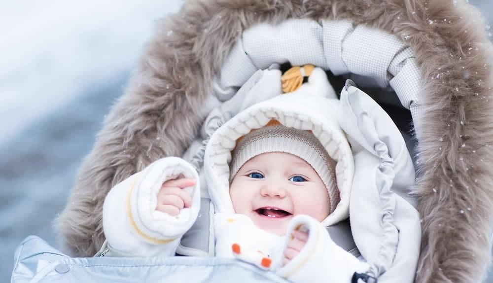 Ein dick eingepacktes Baby im Winter sitzt im Kinderwagen