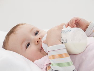 Ein Baby im Bettchen mit seinem Fläschchen