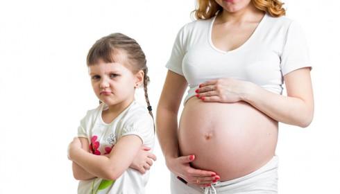 Ein beleidigtes Kind steht vor einer schwangeren Frau