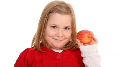 Ein Mädchen hält einen Apfel