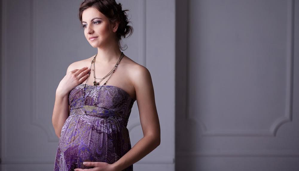 Eine schwangere Frau trägt ein langes, lilafarbenes Kleid